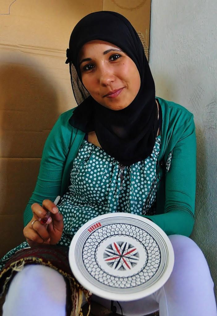 Dívka, která maluje místní keramiku.