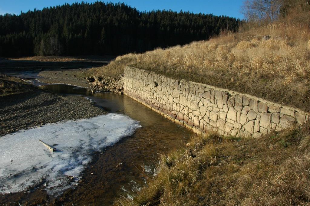Stará kamenná zeď kdysi regulovala tok řeky Ostravice. Dnes je zatopena přehradou.