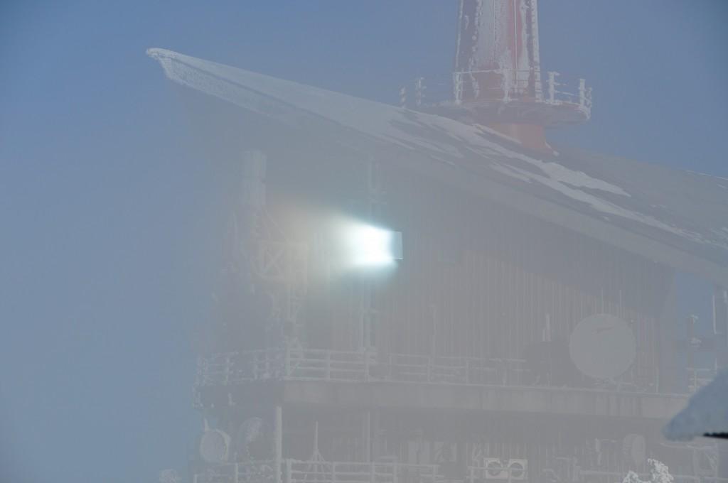 Slunce proráží mlhu na vrcholu Lysé hory. A odráží se v okně vysílače.