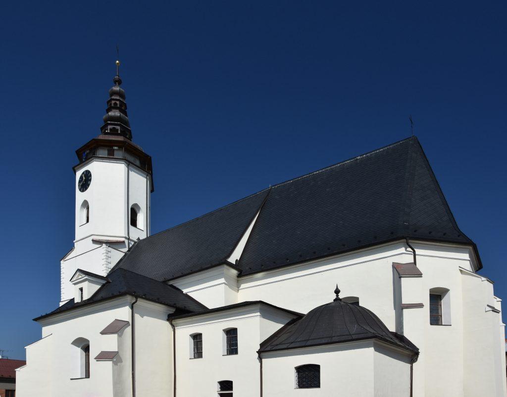 Kostel svatého Mikuláše. Bílá fasáda ostře kontrastuje s modří podzimní oblohy.