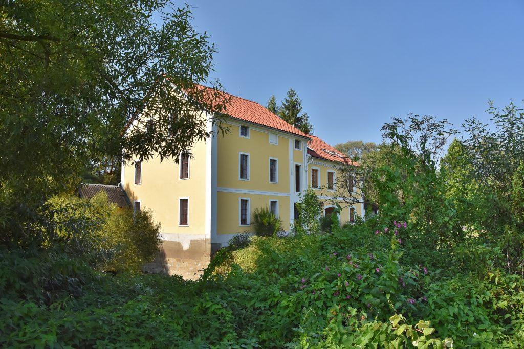 Bartošovický mlýn je ukryt v zeleni. Skoro to vypadá jako království ukryté v šípkovém keři.